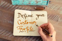 Handwritten text DEFINE YOUR CUSTOMER PROFILE - stock photo