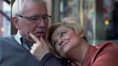 Middle aged senior couple kissing and hugging in cafe in the city - stock footage