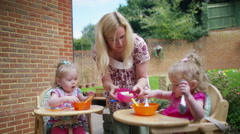 4K Mother feeding toddler twins in high chairs in the backyard - stock footage