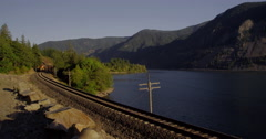 A freight train rumbles along the Washington State side of the Columbia River Stock Footage