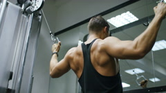 Young man using a cable pulley machine in the gym, in slow motion Stock Footage