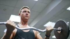 Muscular young man doing bicep curls with a barbell - stock footage