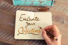Handwritten text EVALUATE YOUR OBJECTIVES - stock photo