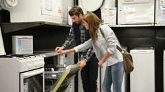 Seller helping customer with choosing dishwasher - stock footage