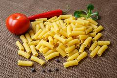 Rigatoni raw pasta on background of jute - stock photo