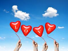 Hand holding a red heart balloons. Stock Photos