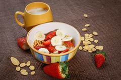 Healthy breakfast. Cornflakes, fresh strawberries, banana and milk Stock Photos