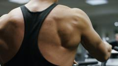Back of a muscular man working out in the gym, in slow motion - stock footage