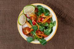 Bowl of fresh vegetable salad on jute table cloth Stock Photos