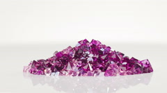 Violet jewel stones heap turning over white background Stock Footage