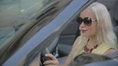 Attractive woman with red lipstick starts the car Stock Footage