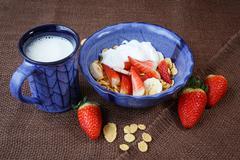 Healthy breakfast. Cornflakes, fresh strawberries, banana, yogurt and milk Stock Photos
