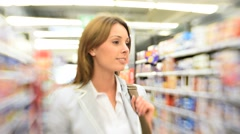 Beautiful woman walking in supermaket aisle Stock Footage