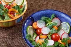 Bowls of fresh vegetable salad on jute table cloth - stock photo
