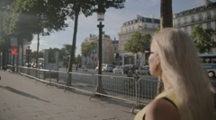Beautiful woman in sunglasses wearing a dress going along the street - stock footage