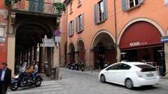 Cars pass by the street with historical buildings in Bologna, Italy. Stock Footage