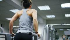Young female doing tricep dips in a gym Stock Footage