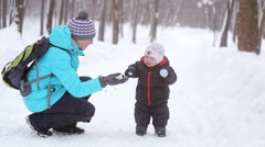 Young mother walking in the Park with the child, snow day - stock footage