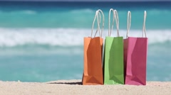 Shopping bags on sand against turquoise caribbean sea Stock Footage