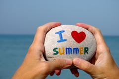 Stone with words I love summer in person hands - stock photo