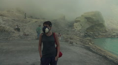 Woman in gas mask standing in Ijen volcano crater, Indonesia, slow motion Stock Footage