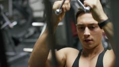 Muscular young man using a weights machine in the gym Stock Footage