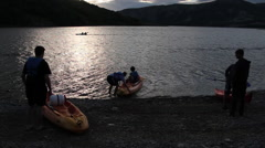 Canoes entering lake at sunset Stock Footage