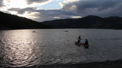 Several canoes paddling on lake at sunset Stock Footage