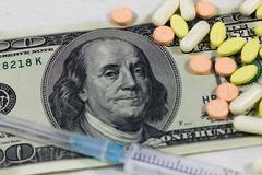 One hundred dollars syringe and pills - stock photo