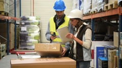 Store manager with warehouseman checking stock levels Stock Footage