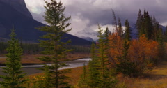 Clearing storm above the Saskatchewan River, its banks lined with fall colors Stock Footage