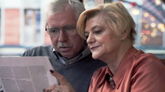 Mature couple reading magazine in cafe Stock Footage