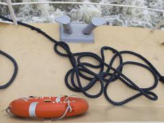 rope and life preserver on deck - stock photo