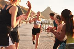 Group of spectators cheering runners at finish line Stock Photos
