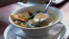 Woman eating thai soup in restaurant Stock Footage