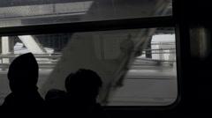 Silhouette of people riding B train across Manhattan Bridge with Brooklyn Bridge Stock Footage