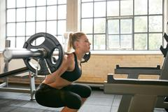 Female working out in a gym doing squats Kuvituskuvat