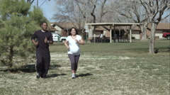 Man and pregnant woman jogging through the park together. Stock Footage