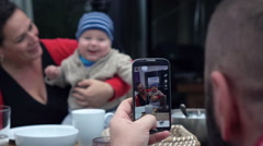 Father taking photo with cellphone of his wife and son, super slow motion Stock Footage