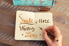 Handwritten text SMILE MORE WORRY LESS Stock Photos