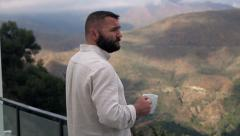 Sad, pensive man drinking wine on terrace with country mountains view Stock Footage