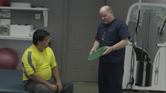 Physical therapist working with patient on grip exercise. - stock footage