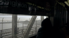 Silhouette of lonely man in hat and coat looking moving subway window East River Stock Footage