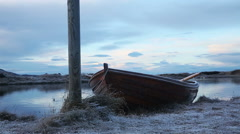 Iceland boat at frozen lakes edge sliding scene Stock Footage