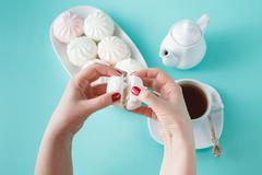 Stock Photo of Women burst colored marshmallow for breakfast
