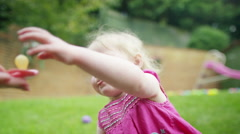 4K Portrait of little girl with pacifier & soft toy sitting in the garden - stock footage