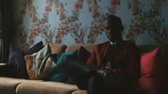 Elegantly Dressed Young Black Man Sitting on Sofa and Answering Cellphone Call - stock footage