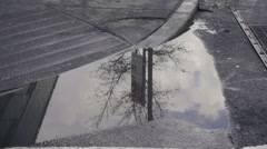 Puddle reflection of 8th street in winter snow tilting up to people in NYC Stock Footage