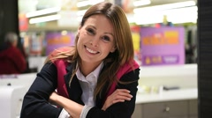 Customer service woman standing at the reception desk of supermarket - stock footage