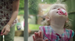 4K Cute little girl with cleaning cloth cleaning window from outside - stock footage